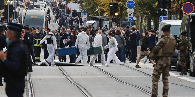 Forensics officers deploy stretchers at the site of a knife attack as French soldiers stand guard the street in Nice. (VALERY HACHE/AFP via Getty Images)
