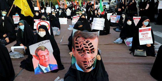 Iranian protesters hold defaced pictures of French President Emmanuel Macron during a protest against Macron and the publishing of caricatures of the Prophet Muhammad they deem blasphemous, in front of French Embassy in Tehran, Iran, Wednesday, Oct. 28, 2020. (AP Photo/Ebrahim Noroozi)