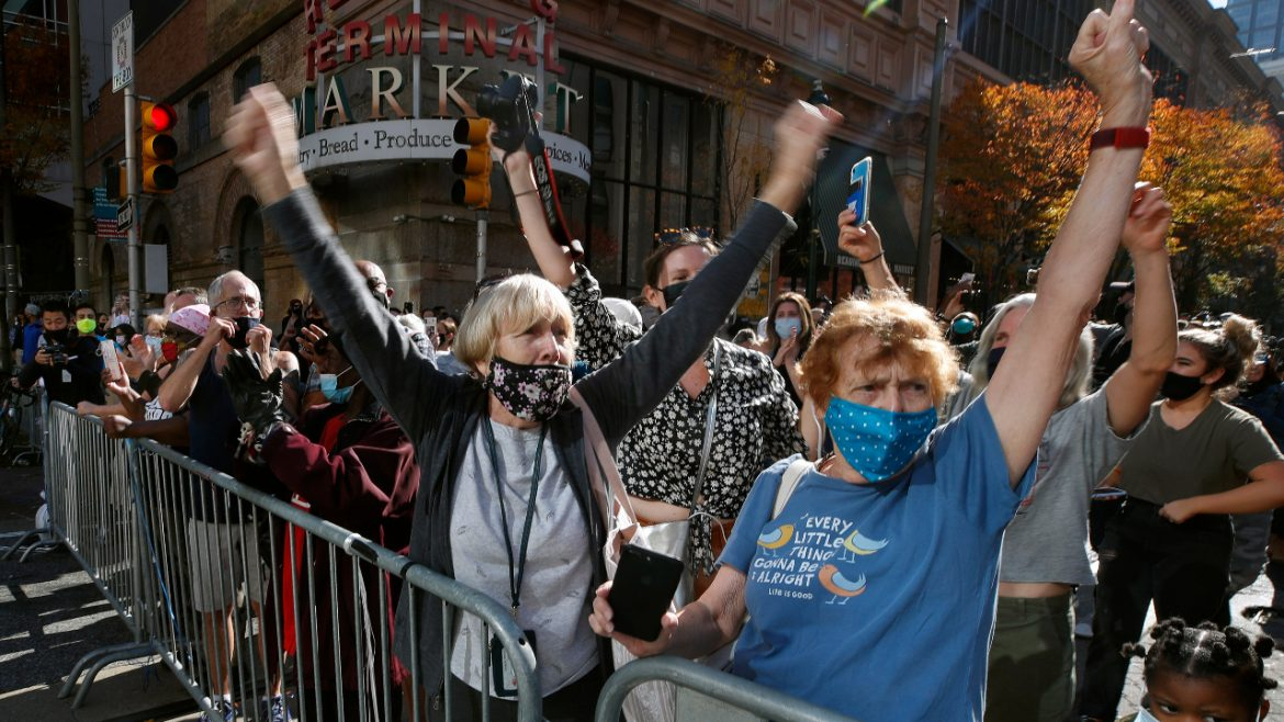 Masked Biden supporters suspend social distancing to cheer his victory