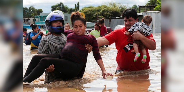 A pregnant woman is carried out of an area flooded by water brought by Hurricane Eta in Planeta, Honduras.