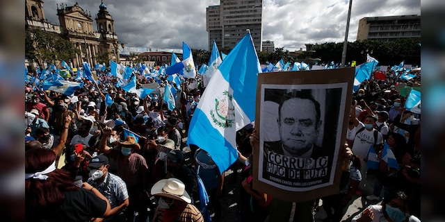 Protesters gather outside Congress in Guatemala City, Saturday, Nov. 21, 2020. Hundreds of protesters were protesting in various parts of the country Saturday against Guatemalan President Alejandro Giammattei and members of Congress for the approval of the 2021 budget that reduced funds for education, health and the fight for human rights. (AP Photo/Moises Castillo)