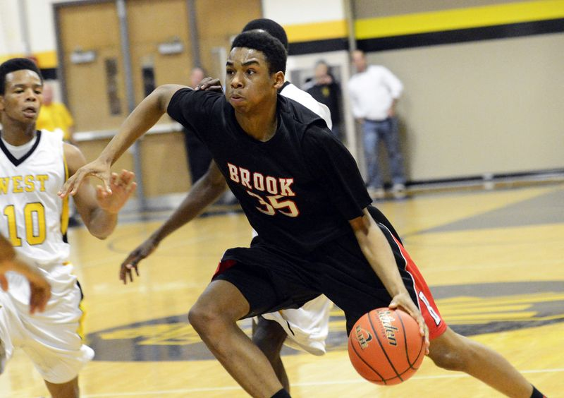 Bolingbrook's Ben Moore (35) drives to the basket in front of Joliet West's Morris Dunnigan (30) in 2012.