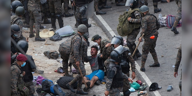 A Honduran migrant is tended to by Guatemalan soldiers after they clashed with them in a bid to reach the U.S. border in Vado Hondo, Guatemala, Sunday, Jan. 17, 2021. Guatemalan authorities estimated that as many as 9,000 Honduran migrants crossed into Guatemala as part of an effort to form a new caravan to reach the U.S. border. (AP Photo/Sandra Sebastian)