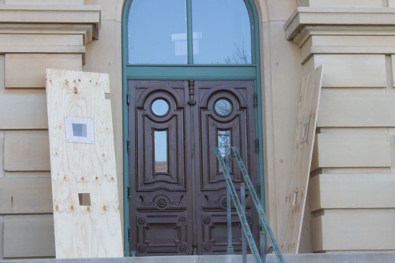 Plywood is removed from a door at the Illinois State Capitol on Thursday,