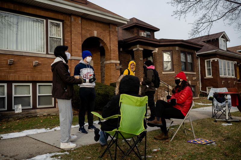 Chicago Public Schools alums Genesis Rivera (left) and Diego Garcia (blue hat) stand with teachers Wednesday morning outside the Belmont Cragin home of Miguel del Valle, president of the Chicago Public Schools board, on Wednesday, Jan. 13, 2021.