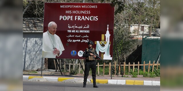 Security stand by a poster depicting Pope Francis, in Baghdad Iraq, Friday, March 5, 2021. Pope Francis heads to Iraq on Friday to urge the country's dwindling number of Christians to stay put and help rebuild the country after years of war and persecution, brushing aside the coronavirus pandemic and security concerns. (AP Photo/Andrew Medichini)