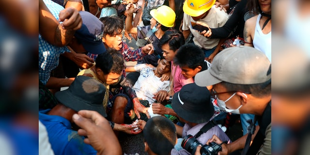 Anti-coup protesters surround an injured man in Hlaing Thar Yartownship in Yangon, Burma Sunday, March 14, 2021. A number of people were shot dead during protests in Burma's largest city on Sunday, as security forces continued their violent crackdown against dissent following last month's military coup. (AP Photo)