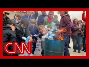 Children burn masks at rally
