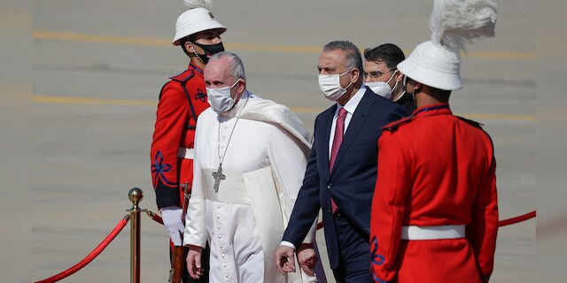 Pope Francis is flanked by Iraqi Prime Minister Mustafa al-Kadhimi upon his arrival at Baghdad's international airport, Iraq, Friday, March 5, 2021. Pope Francis heads to Iraq on Friday to urge the country's dwindling number of Christians to stay put and help rebuild the country after years of war and persecution, brushing aside the coronavirus pandemic and security concerns. (AP Photo/Andrew Medichini)