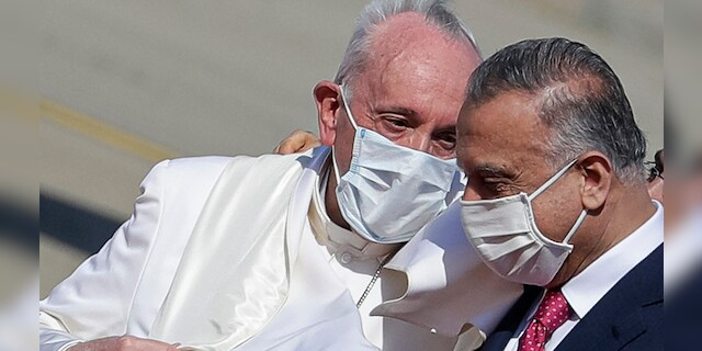 Pope Francis is greeted by Iraqi Prime Minister Mustafa al-Kadhimi as he arrives at Baghdad's international airport, Iraq, Friday, March 5, 2021. The pope is seeking to deliver a message of reconciliation and fraternity, a tough sell given the few Christians who remain in Iraq harbor a lingering mistrust of their Muslim neighbors and face structural discrimination that long predated IS and the 2003 U.S.-led invasion that threw the country into chaos. (AP Photo/Andrew Medichini)