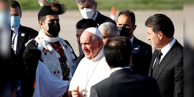 Iraqi Kurds officials welcome Pope Francis, center, as he arrives at Irbil airport, Iraq, Sunday, March 7, 2021. (Associated Press)