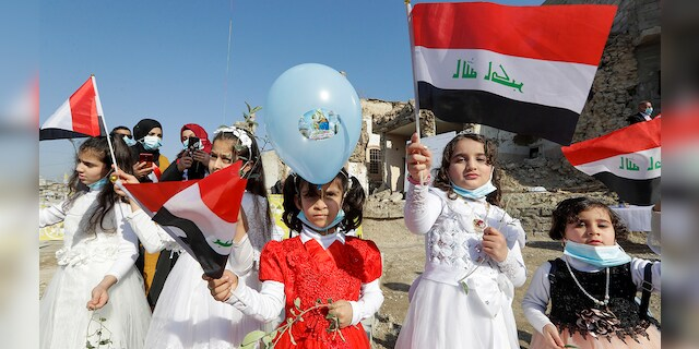 Children in their festive garment wave Iraqi flags to the camera as they arrive to join Pope Francis who will pray for the victims of war at Hosh al-Bieaa Church Square, in Mosul, Iraq, once the de-facto capital of IS, Sunday, March 7, 2021. (Associated Press)