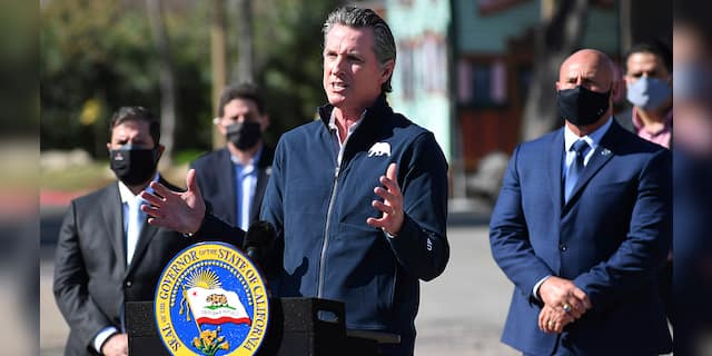 California Gov. Gavin Newsom, center, gestures in front of local officials while speaking about COVID-19 vaccines at the Fresno Fairgrounds, Wednesday, Feb. 10, 2021, in Fresno, Calif. Newsom, widely accused of hypocrisy including for putting his children in in-person school and dining indoors against his own health guidance, is facing a likely recall election. (John Walker/The Fresno Bee via AP)