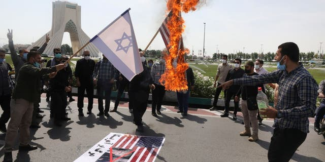 Demonstrators burn representations of Israeli and U.S flags during the annual Al-Quds, or Jerusalem, Day rally, with the Azadi (Freedom) monument tower seen at left, in Tehran, Iran, Friday, May 7, 2021.