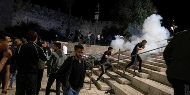 Palestinians react to stun grenades fired by Israeli police to clear the Damascus Gate to the Old City of Jerusalem after clashes at the Al-Aqsa Mosque compound, Friday, May 7, 2021. Palestinian worshippers clashed with Israeli police late Friday at the holy site sacred to Muslims and Jews.