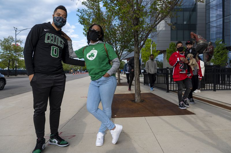 Boston Celtics fans, Chris Fisher, left, and Karen Fisher, pose together outside the United Center, during the first home game allowing fans to spectate between the Bulls and Boston Celtics.