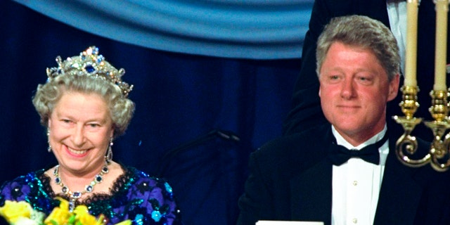 In this Saturday, June 4, 1994, file photo, Britain's Queen Elizabeth smiles as she sits alongside President Bill Clinton at a dinner in the Guildhall in Portsmouth, England, commemorating the 50th anniversary of D-Day. (AP Photo/Doug Mills, File)