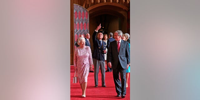 In this June 15, 2008, file photo, Queen Elizabeth II and Prince Philip, the Duke of Edinburgh, pointing, walk with U.S. President George Bush and his wife Laura, in St George's Hall, Windsor Castle, in Windsor, England. (Nick Ray, Pool Photo via AP, File)