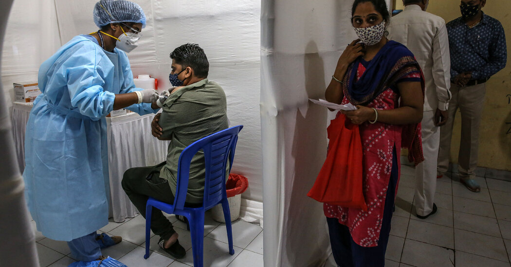 India hits a milestone, giving vaccine shots to more than half of the eligible population.