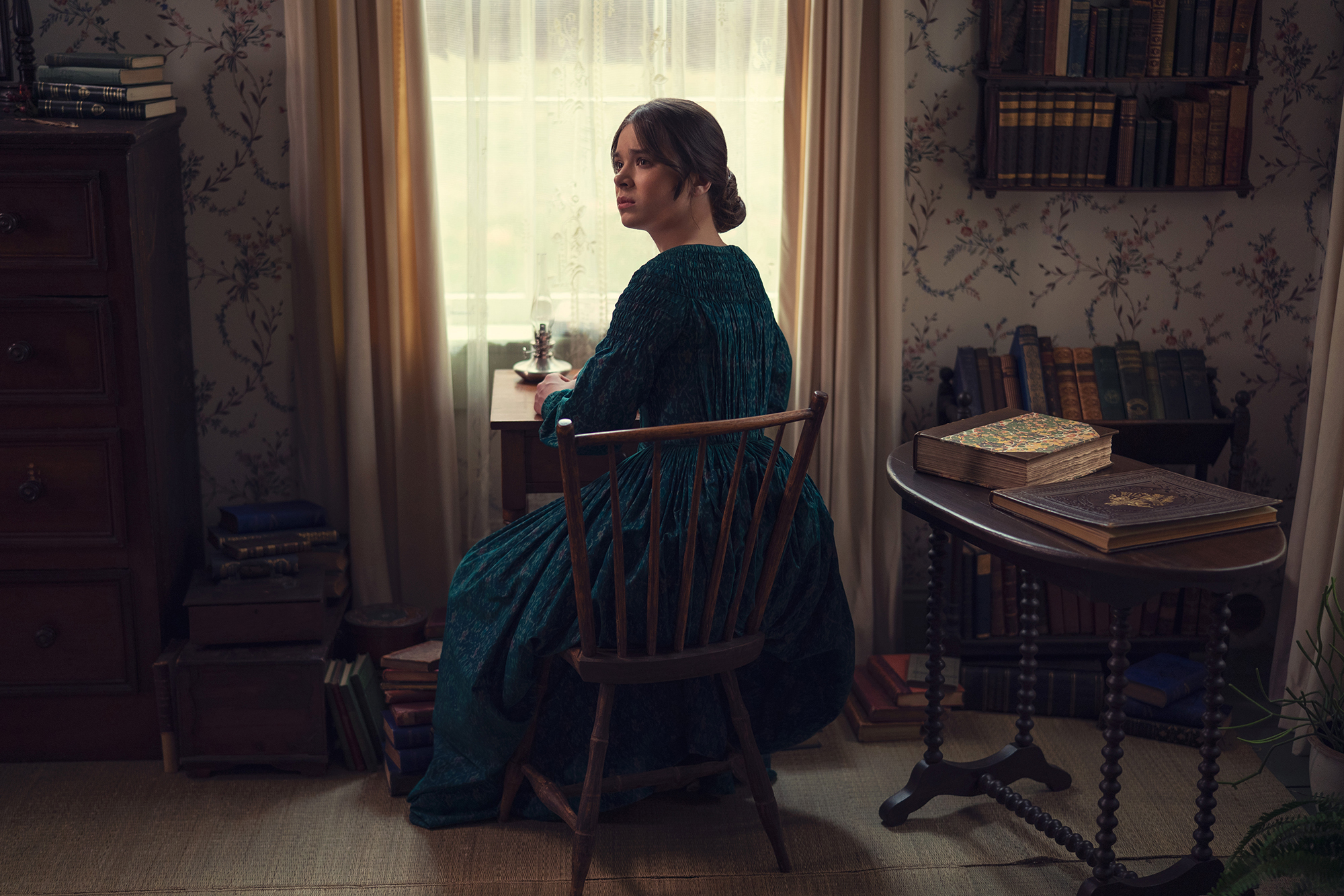 Hailee Steinfeld as Emily Dickinson wears a dress and sits at a desk in a dim room with her back to the camera.