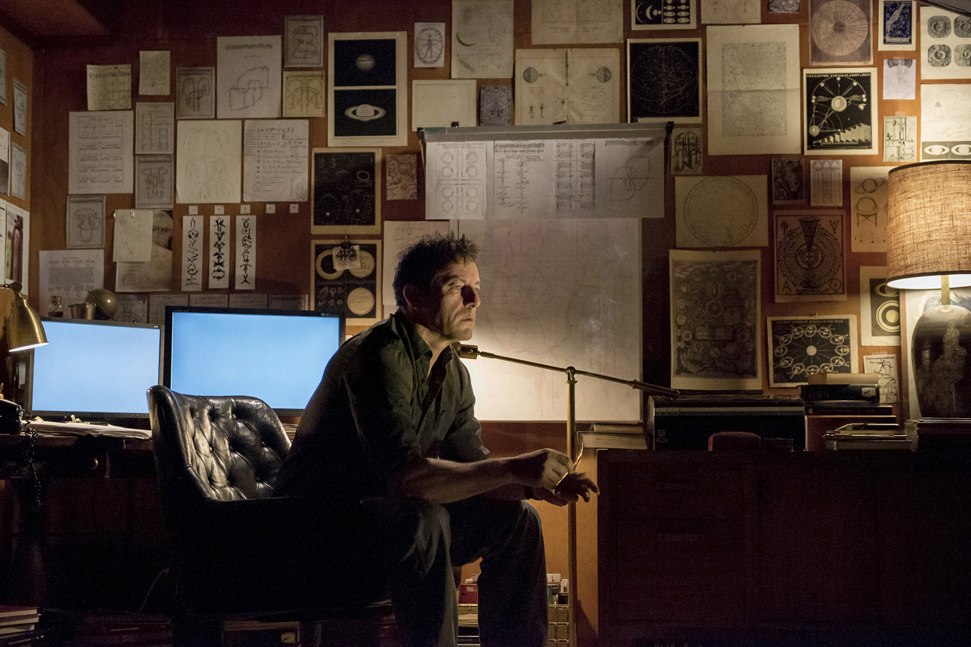 Jason Isaacs sits on a chair in a room lined with newspaper clippings on the walls