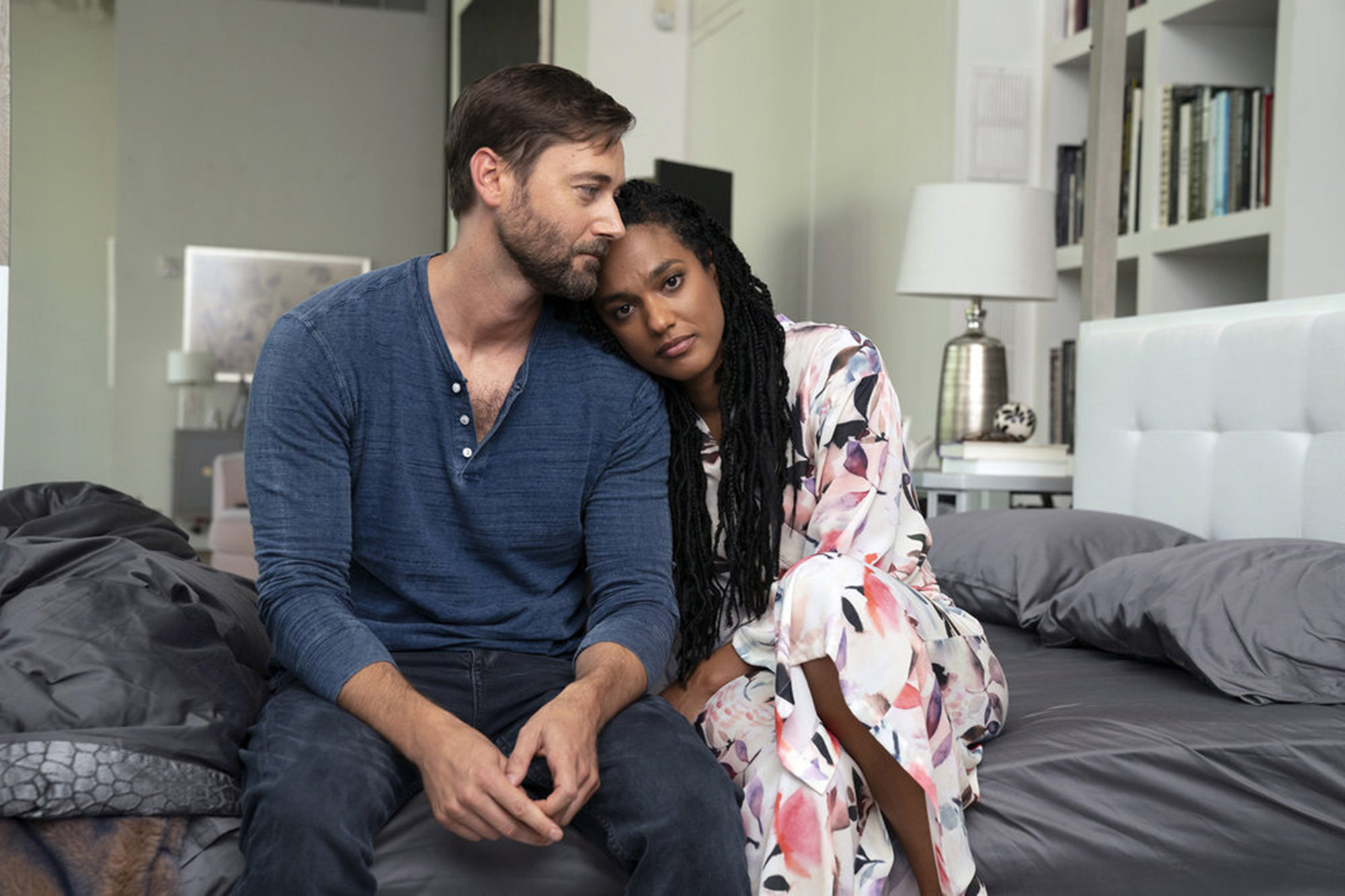 """Ryan Eggold as Max sits on a bed and leans against Freema Agyeman as Helen in """"New Amsterdam."""""""